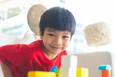Asian boy stacking Toy blocks on a living room table