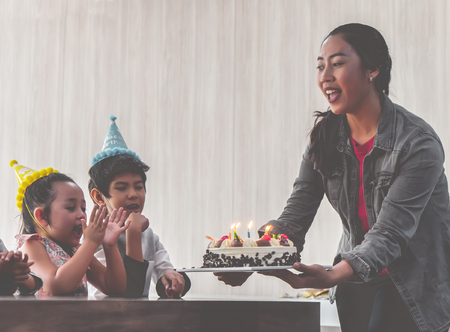 Group of children is blowing birthday cake in birthday party singing happy birthday