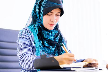 Muslim woman is using digital tablet on office table