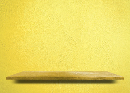 Empty wooden shelf on yellow cement wall Stock Photo