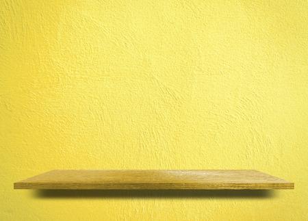 Empty wooden shelf on yellow cement wall 写真素材