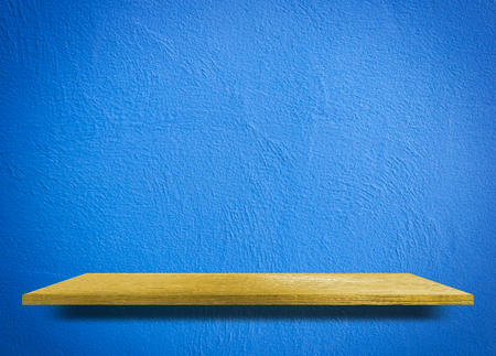 Empty wooden shelf on blue cement wall Stock Photo