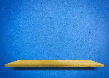 Empty wooden shelf on blue cement wall 写真素材