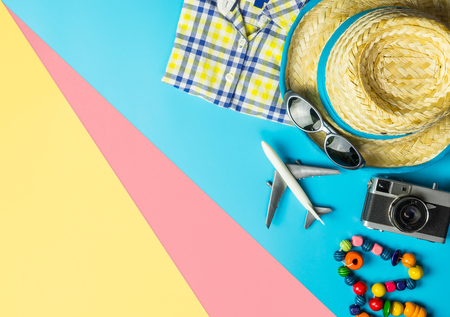 Summer travel fashion and accessories on blue pink yellow background