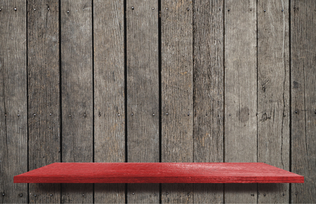 Empty red wooden shelf on brown wooden wall
