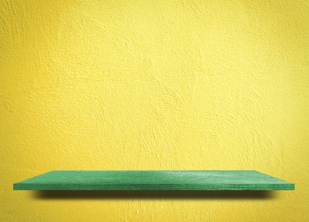 Empty green wooden shelf on yellow cement wall