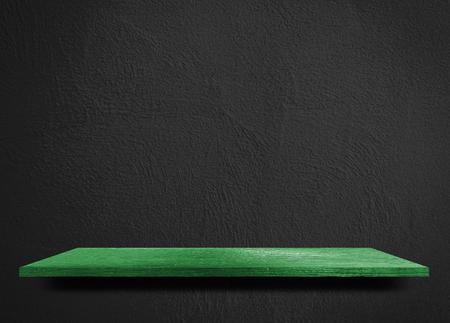 Empty green wooden shelf on black cement wall Stock Photo