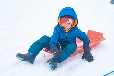 Little Japanese boy is sliding down the snow sled in Gala Yuzawa Ski resort 免版税图像