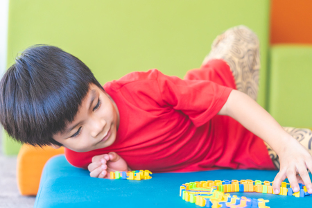 little boy learning to play hard puzzle toy 版權商用圖片