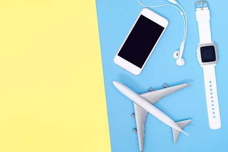 Travel accessories objects and gadgets top view flatlay on blue yellow Stock Photo