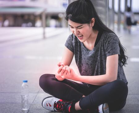 Sport woman is having an injury on her wrist hand Reklamní fotografie