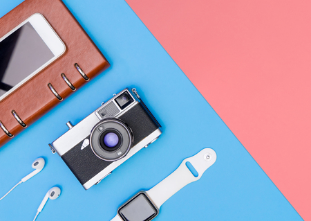 Travel accessories objects and gadgets top view flatlay on blue pink