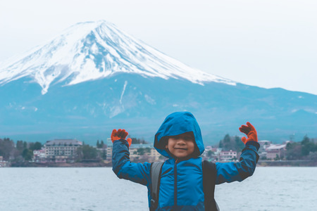 Kid is standing in front of Kawaguchiko lake and mount fuji in winter. 版權商用圖片