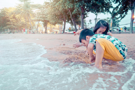 Two siblings children is playing with wave and sand in Pattaya Beach Thailand Фото со стока - 124374730