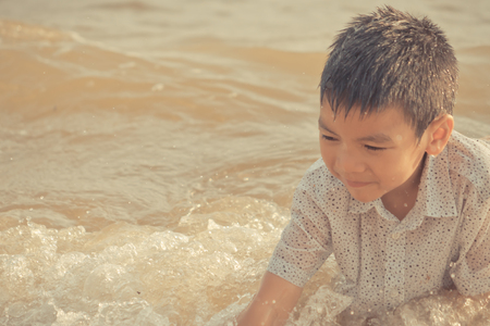 Little boy is playing with wave and sand on Pattaya beach Фото со стока - 122712675