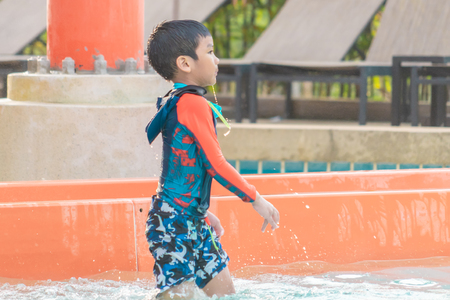 Asian boy playing next to a water slide in aqua water park Stock Photo