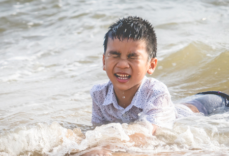 Little boy is playing with wave and sand on Pattaya beach Standard-Bild - 123203092