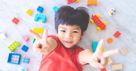 Gelukkige jongen omringd door kleurrijke speelgoedblokken bovenaanzicht V-vorm hand voor overwinning