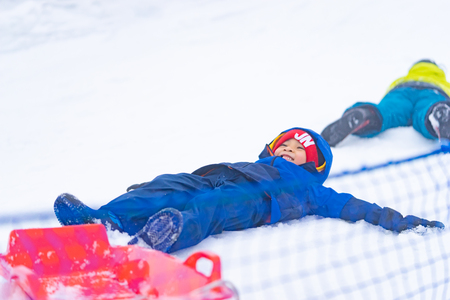 Little boy is lying down on snow 스톡 콘텐츠 - 123203134