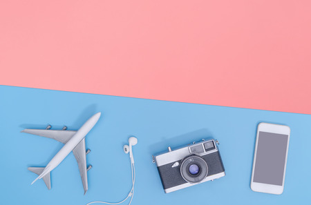 Travel accessories objects and gadgets top view flatlay on blue pink yellow copy space