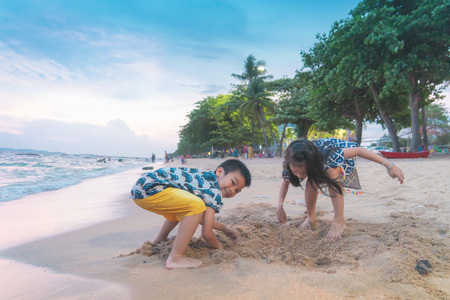 Two siblings children is playing with wave and sand in Pattaya Beach Thailand