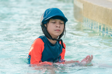 Little girl is playing in swimming training pool, wiping water out of her face