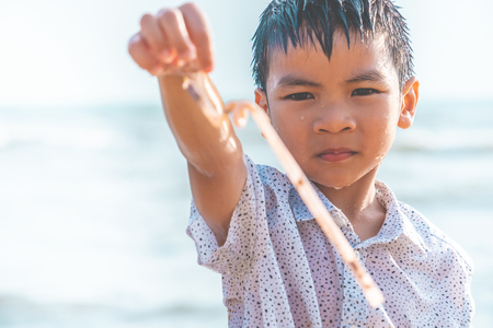 Children is holding Plastic straw that he found on the beach Foto de archivo - 123203174