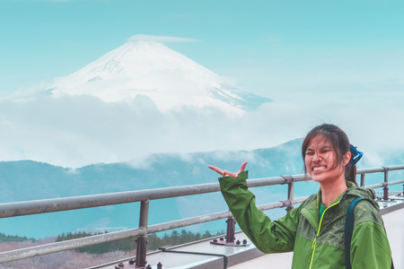 Female tourist is posting hand with Mount Fuji on the background