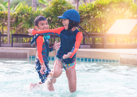Asian siblings is running and chasing in Swimming pool