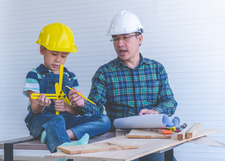 Builder Father is teaching his son to read the construction plan paper.