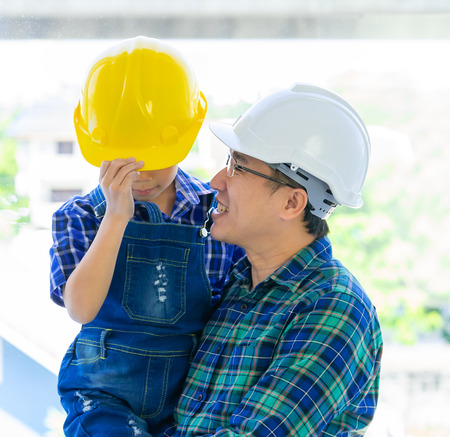 Builder Father holding his son with engineering protecting hat for father day concept. Reklamní fotografie