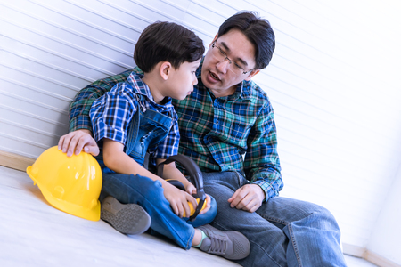 Builder father is sitting next to his son for family connection concept. Reklamní fotografie