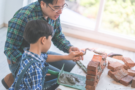Little boy is learning how to lay down brick work from his builder father
