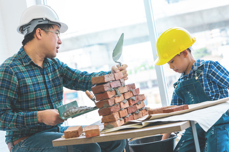 Little boy is learning how to build brick wall from his construction father