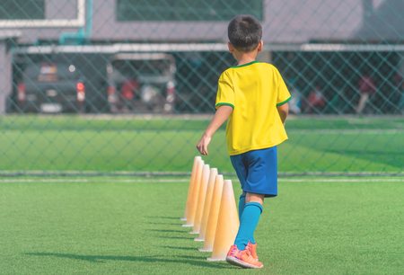 Soccer Boy is training alone with cone on training ground
