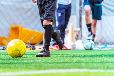 Kinderen trainen en dibbelen bal in voetbaltraining