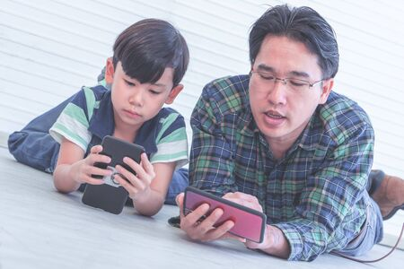 Asian Father is teaching his son to use the smartphone and internet on the floor