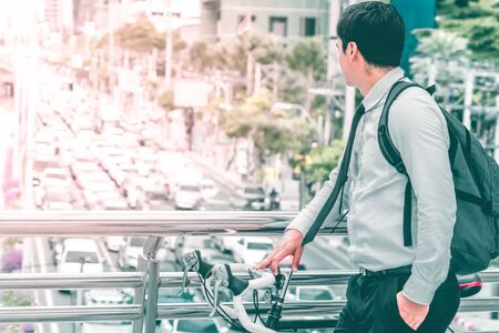 Modern Business man choosing to ride bike to work to avoid Bangkok traffic jam Stock Photo