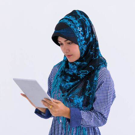 Muslim woman is using digital tablet isolated on white