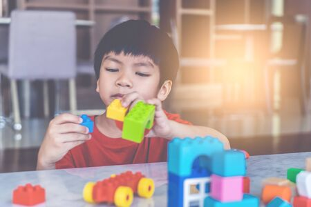 Happy boy stacking Toy blocks on a living room for educational toy Stockfoto