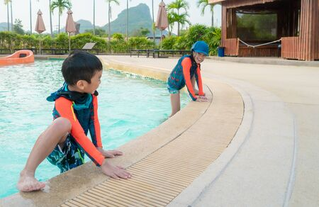 Two Asian siblings in playing together in Water Aqua park pool.