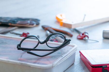 Eye Glasses on handy man construction tool kits on the floor