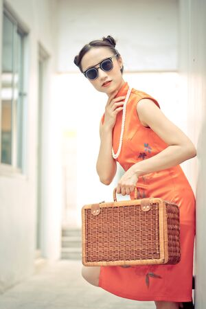 Vintage Chinese fashion model with sunglasses and travel luggage for travel concept