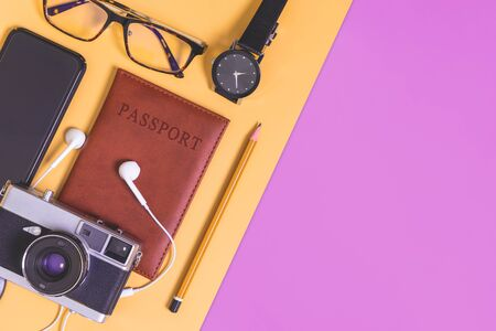 travel objects and accessories on orange brown purple green background with passport camera Reklamní fotografie