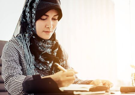 South East Asian islam woman is writting on a book