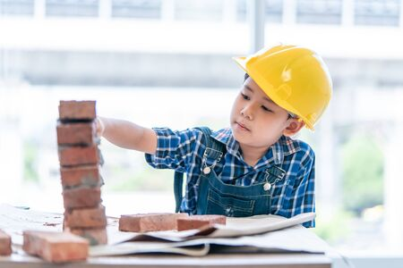Little Builder boy is learning how to build brick wall Stok Fotoğraf