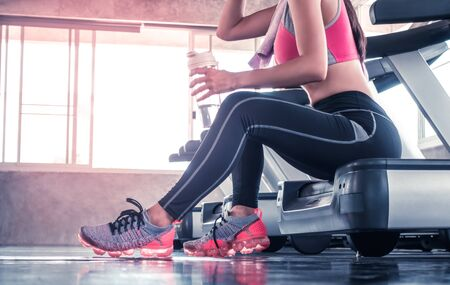 Woman is drinking water on treadmill workout in fitness gym unrecognized face Stok Fotoğraf