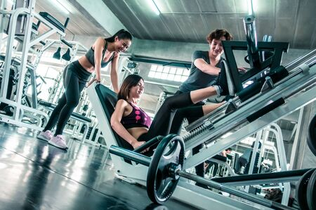 Team of friends is working out Leg Press in fitness gym together, cheering each other