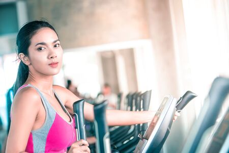 Female in pink sport wear is working out on Step climber machine in fitness gym for healthy lifestyle concept portrait