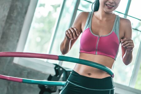unrecognized Female in pink sportwear is working out with  in fitness gym for healthy lifestyle concept Banque d'images